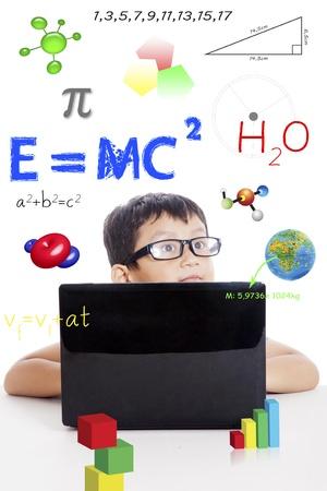 Portret van slimme jongen met natuurkunde formule en laptop computer