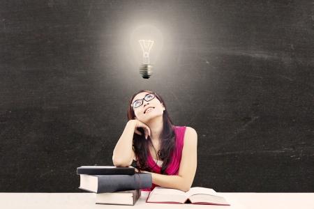 vzdělání: Portrét inteligentní žena student s knihami a žárovkou nad hlavou jako symbol skvělých nápadů