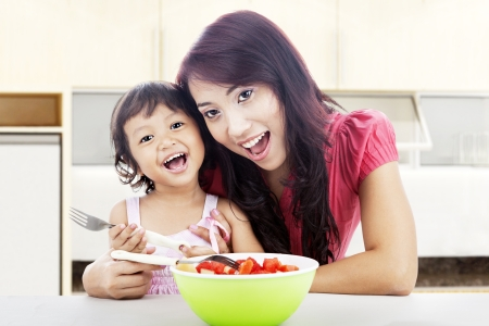 Smiling young asian mother and her daughter with fruit salad. shot in the kitchen photo