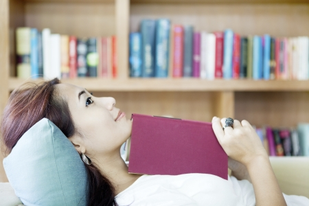 Portrait of smiling woman holding book and lying on couch photo