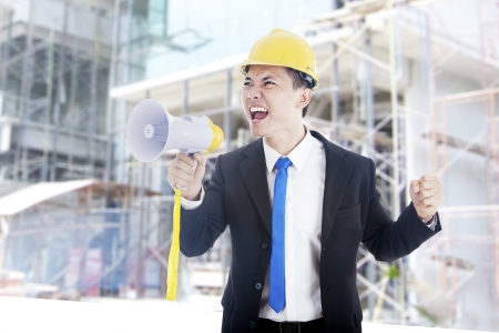 An engineer yelling through a megaphone shot outdoor at construction site photo