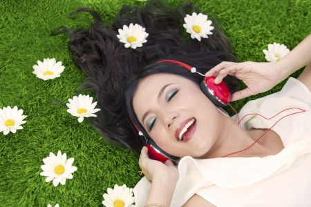 Beautiful woman listens to music while laying on the grass with flowers photo