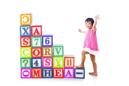 stepping: Portrait of cute little female preschooler stepping upward on alphabet block. isolated on white