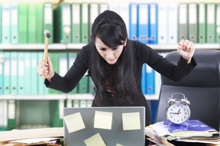 oficina desordenada: Empresaria asiática gritar a su computadora portátil mientras que lleva un martillo