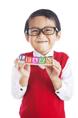 Portrait of asian elementary school student showing letter blocks spelling out LEARN. shot in studio isolated on white  photo