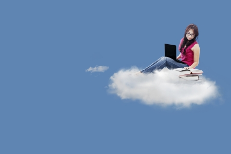 Female college student studying on the cloud by using laptop computer and textbooks photo