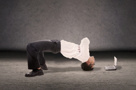 Aantrekkelijke zakenman doet breakdance stijl met laptop computer