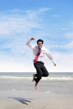 Young businessman jumping at the beach to celebrate his success photo