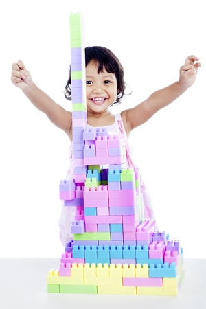 lego: Happy young little girl expressing her success to build with blocks Stock Photo