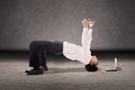 Attractive businessman break dancing with thumbs-up and laptop computer. shot in studio photo
