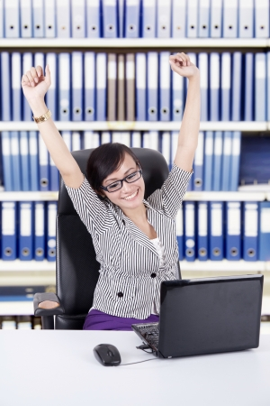 Happy Asian Business woman expressing her success by stretching her hands, shot at office photo