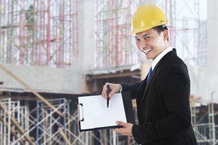 Smiling supervisor showing blank clipboard shot at workplace outdoor photo