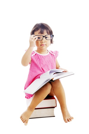 Portrait of sweet asian female kindergarten pupil wearing glasses with book sitting on a pile of books photo
