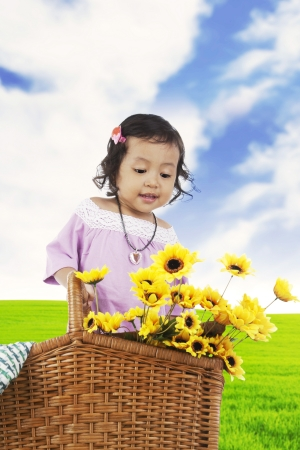 Sweet little girl in a meadow with sunflowers on the basket photo