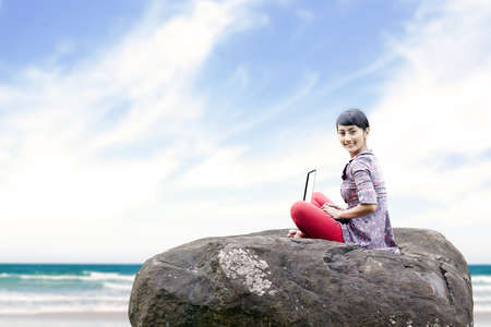 Beautiful woman working on laptop at the beach. shot outdoor Stock Photo - 14779122