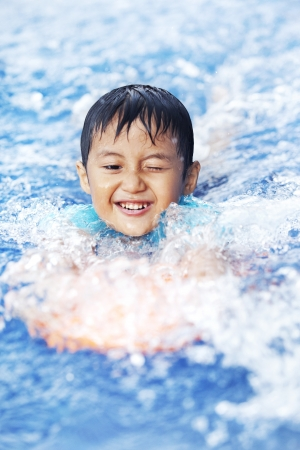 Asian boy learns how to swim shot in summer photo
