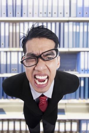 jefe enojado: Hombre de negocios joven con cara de enojo gritando hacia delante, tiro en la oficina Foto de archivo