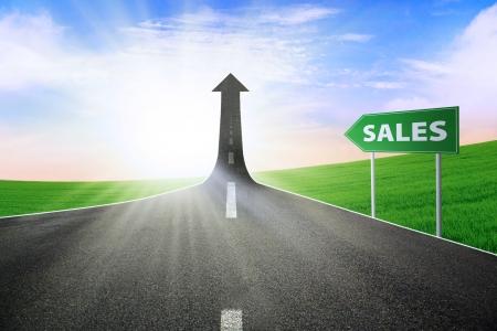 verhogen: Een weg verandert in een pijl omhoog komt met een verkeersbord van de omzet, als symbool van de manier om de verkoop te verbeteren