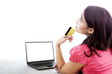 Young woman using credit card for online shopping with copy space on laptop computer photo