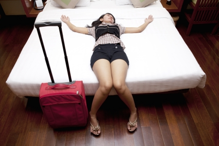 Tired young female traveler sleeping on the bed by stretching her hand photo