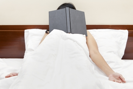 Tired woman sleeping on the bed after read a book with face covered by the book  photo