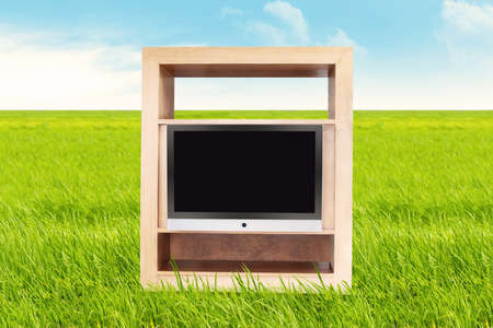 TV with blank screen on the meadow. shot outdoor during summer photo