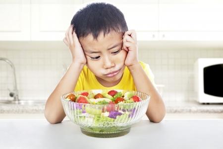 perezoso: Cara expresi�n de ni�o perezoso para comer ensalada. un disparo en la cocina Foto de archivo