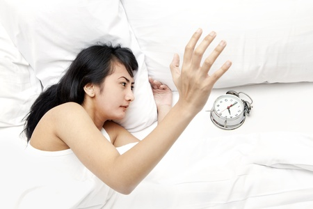 Young woman waking up and hitting alarm clock on the bedroom photo
