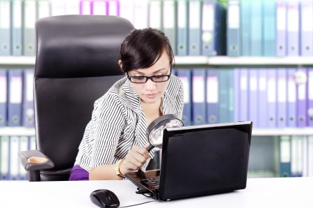 office use: Businesswoman use magnifier for investigate laptop in the office