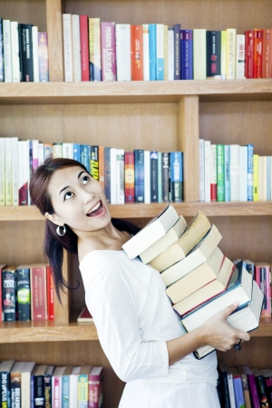 Young attractive asian woman holding a pile of books in front of bookshelf photo