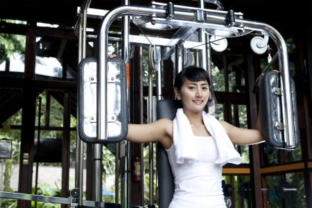 Woman doing fitness training on a butterfly machine with weights in a gym  photo
