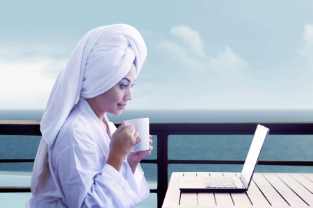 Asian woman in bathrobe holding cup of coffee and looking at laptop computer with ocean view photo