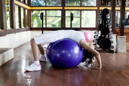Young woman doing fitness exercises using blue swiss ball shot at fitness center photo