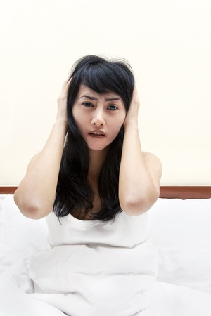 nightmare: Beautiful female sitting in bed, looked having insomnia