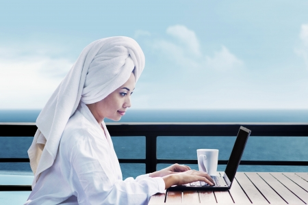 Asian woman in bathrobe with mug of coffee and typing on laptop computer. shot on  ocean view Stock Photo - 15193412