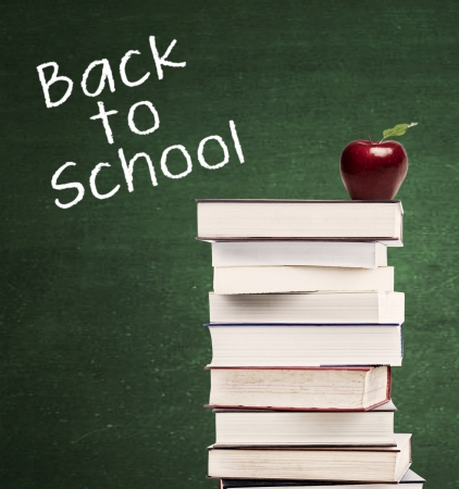 Pile of textbooks with a red apple and a text of Back to School on the blackboard.  photo