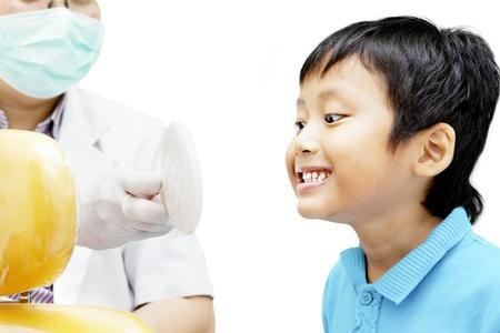 higiene bucal: Retrato de ni�o asi�tico que mira el espejo para revisar sus dientes en la cl�nica dental