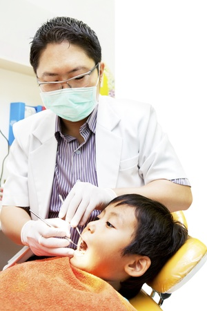 Portrait of asian dentist examining oral cavity of his patient at dental clinic photo