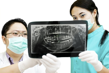 Portrait of male dentist and assistant checking x-ray at dental clinic photo