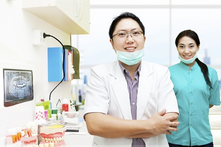 dentist mask: Portrait of male dentist and his assistant in the dentist clinic Stock Photo