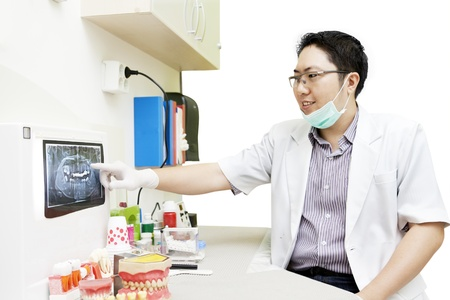 Portrait of male asian dentist pointing at x-ray of teeth in the dentist clinic photo