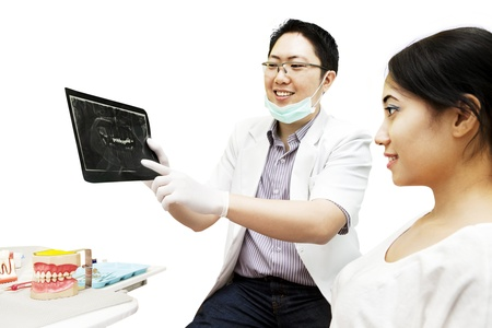 Portrait of asian dentist showing dental x-ray to his patient at dental clinic photo