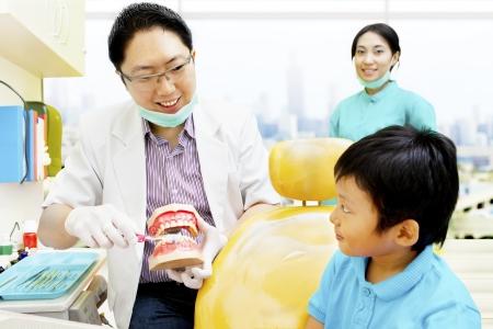 dentist s office: Portret mężczyzny dentysty pokazując właściwą drogę do mycia i utrzymania higienistki stomatologicznej dla chłopca Zdjęcie Seryjne