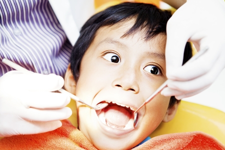 Close-up of little boy opening his mouth wide during inspection of oral cavity by dentist photo