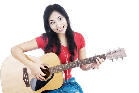 Smiling asian woman playing guitar. shot in studio isolated on white photo