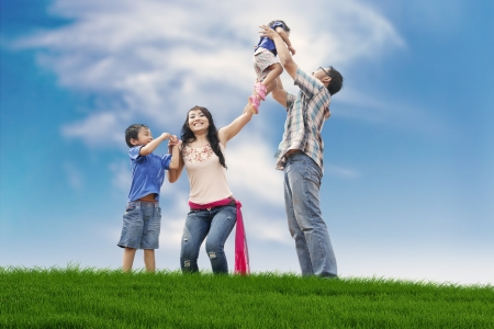 Asian family spending a fun summer day in meadow  Stock Photo
