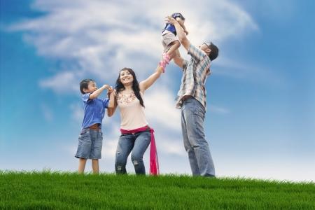 indianin: Azjatycka rodzina spędzać dzień zabawy na łące, lato