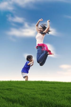Portret van gelukkige moeder en haar dochter springen op de weide. neergeschoten buiten in de zomer Stockfoto