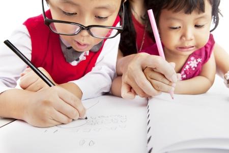 niños estudiando: Retrato de los niños pequeños asiático escribir en el papel. disparado en su casa