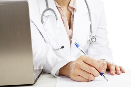 Female doctor with stethoscope and laptop writing on the paper makes a prescription photo